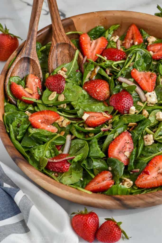 strawberry spinach salad in large bowl with balsamic dressing
