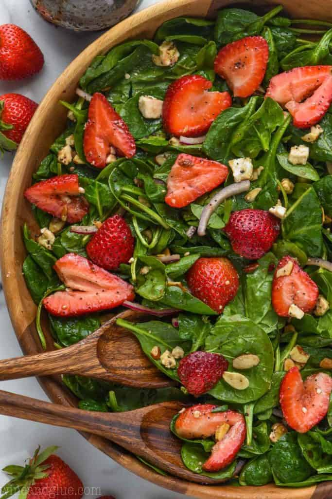 overhead view of strawberry spinach salad in wooden bowl topped with sliced strawberries, red onions, nuts, and balsamic poppyseed dressing.
