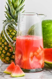 a tall pitcher of watermelon rum punch with a pineapple and a watermelon in the background