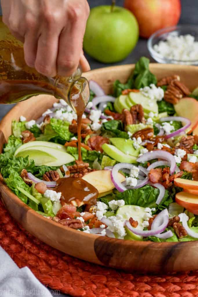 pouring dressing on an apple bacon salad