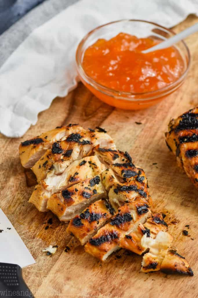 piece of grilled chicken cut up, and in the background is of Apricot Mustard Marinade