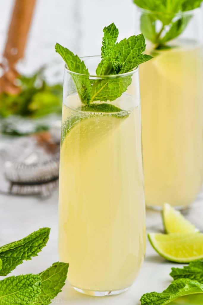 stemless champagne flute with champagne moscow mule, garnished with mint leaves and a lime wedge