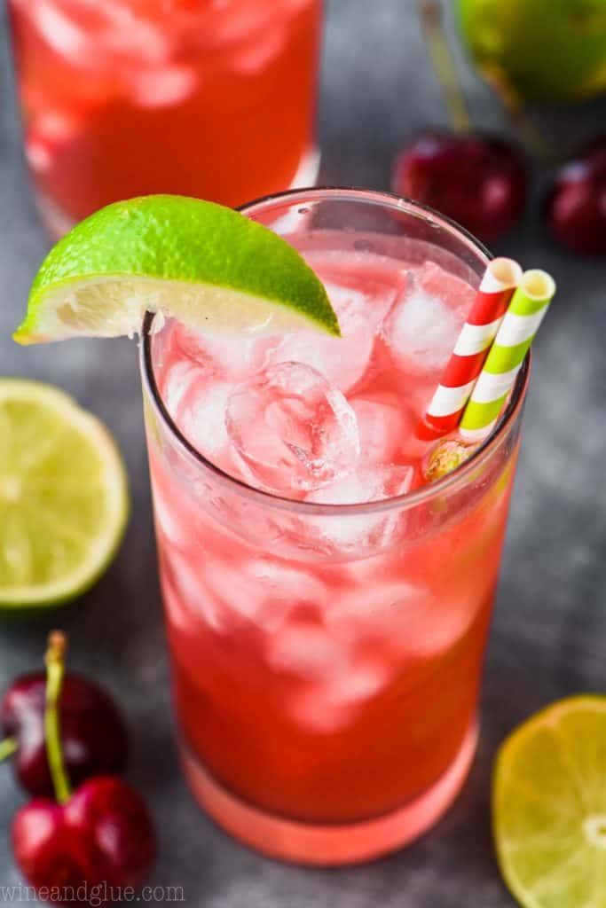 overhead view of a high ball glass with ice, cherry lime vodka tonic, a striped red straw, a striped green straw and a lime wedge