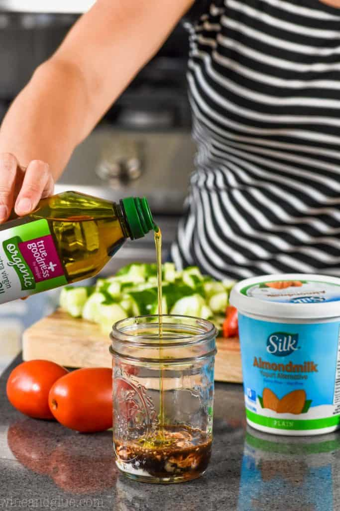 woman pouring olive oil into a mason jar to make creamy balsamic dressing