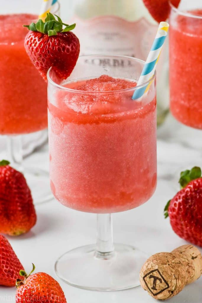 frosted glass of rose with two straws garnished with a strawberry