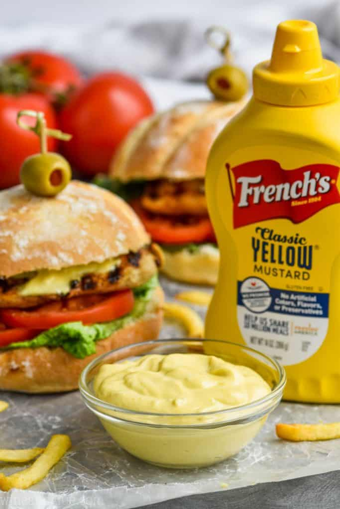 garlic mayonnaise mustard sauce pictured with two chicken sandwiches