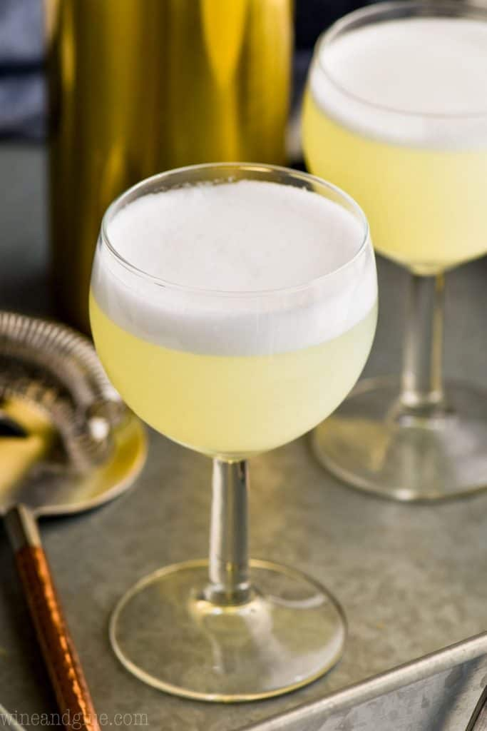small goblet of gin fizz with a frothy egg white top on a metal tray