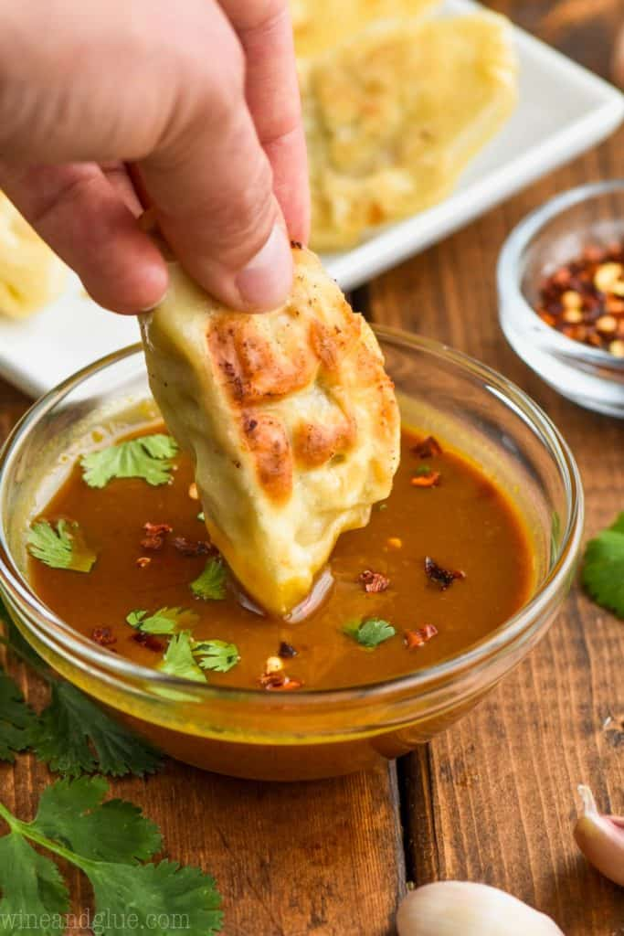 dipping a fried potsticker in potsticker sauce that is topped with red pepper flakes and cilantro