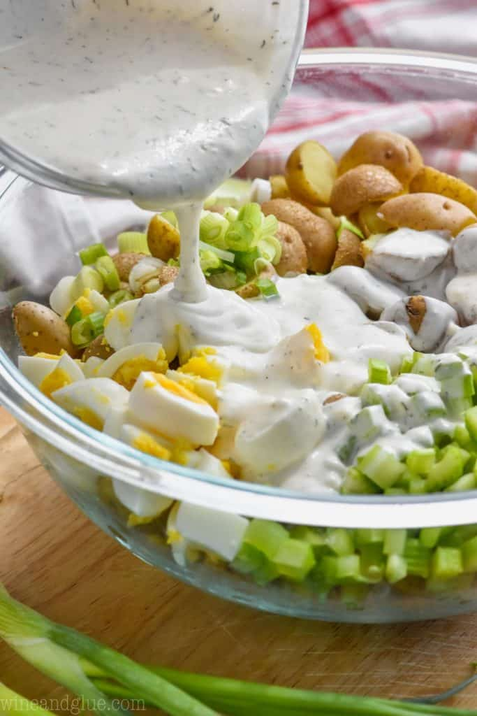 pouring dressing on potato salad