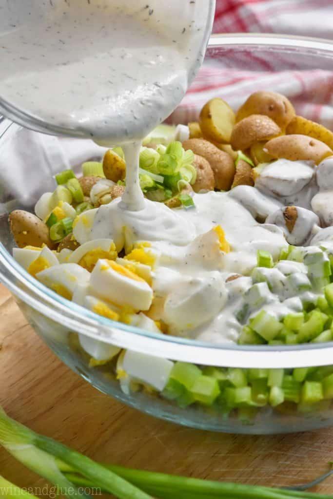 pouring dressing on potato salad
