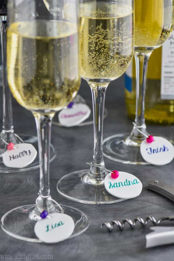 diy wine charms hanging off of champagne glasses