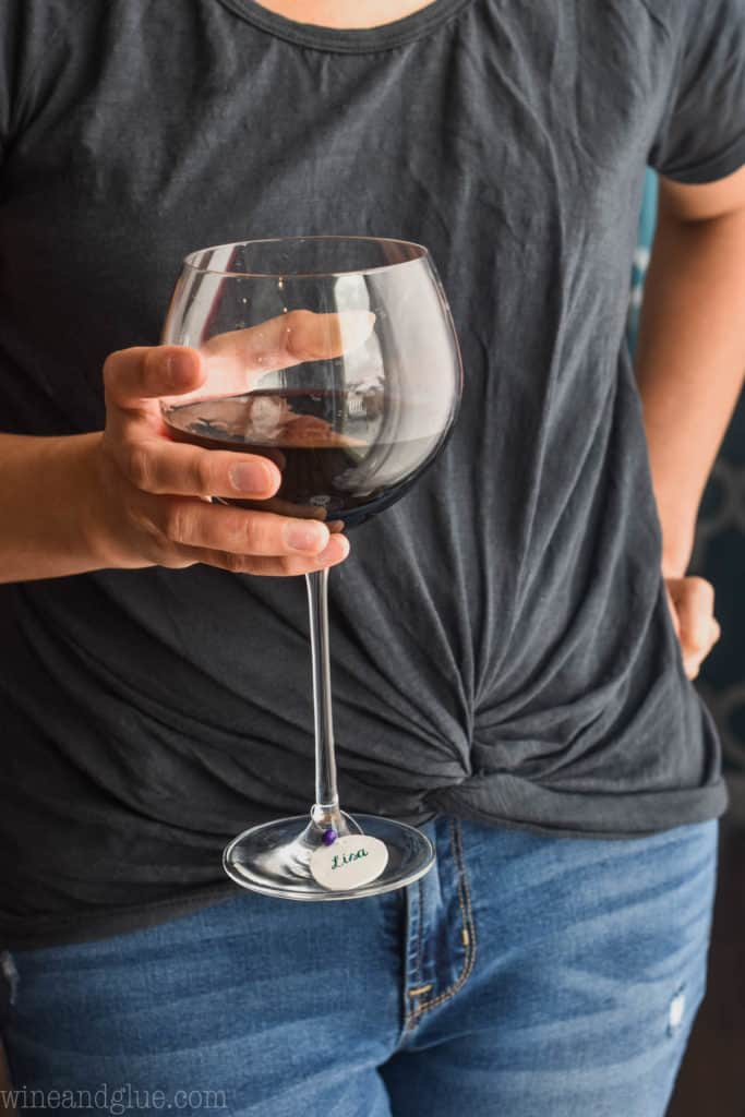 woman holding a red wine glass with a diy wine charm on it
