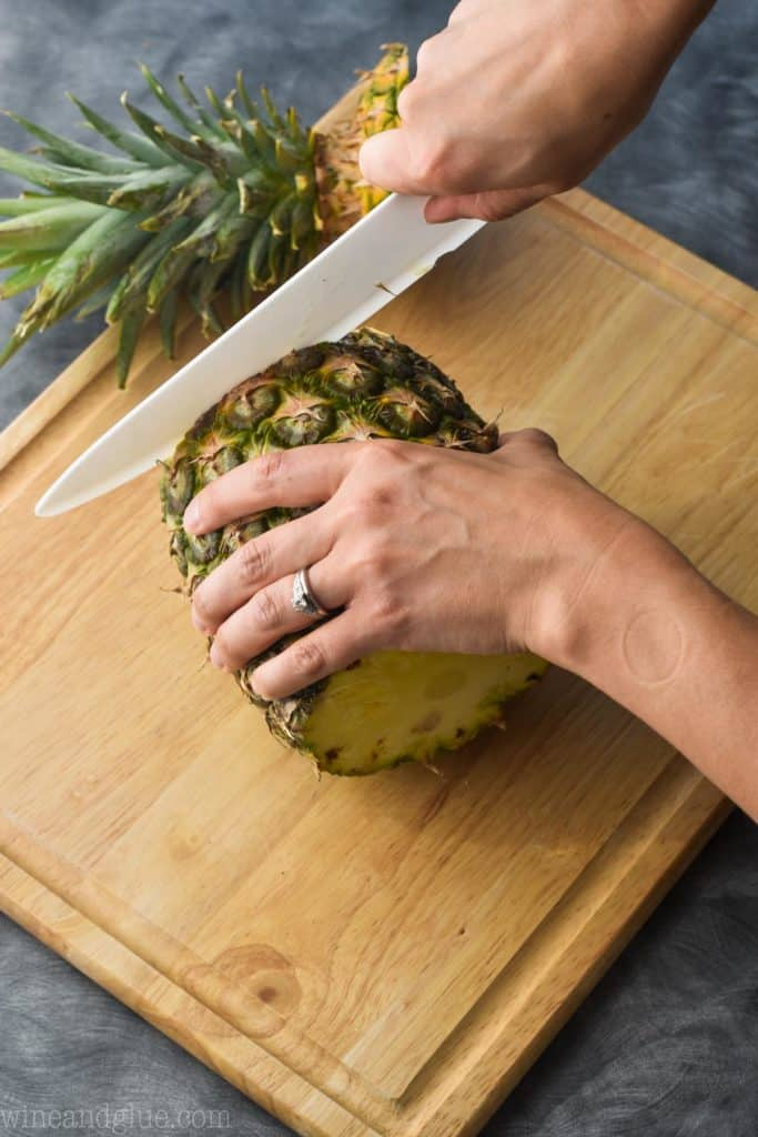 a pineapple on a cutting board with the bottom being cut off
