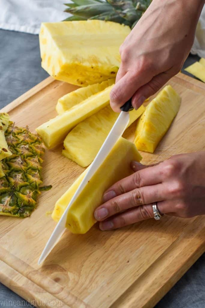 a pineapple being cut into spears on a cutting board