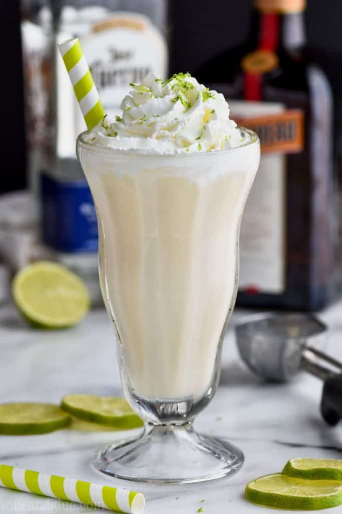 tall milkshake glass filled with margarita boozy milkshake with liquor bottles in the background garnished with lime zest