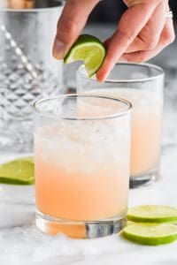 fingers squeezing a lime wedge into a tumbler half filled with ice and a paloma cocktail