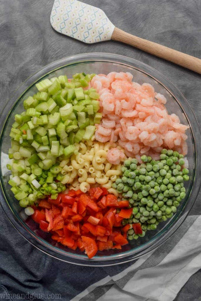 overhead view of shrimp pasta salad ingredients in a bowl (elbow pasta, chives, peas, red peppers, and shrimp)