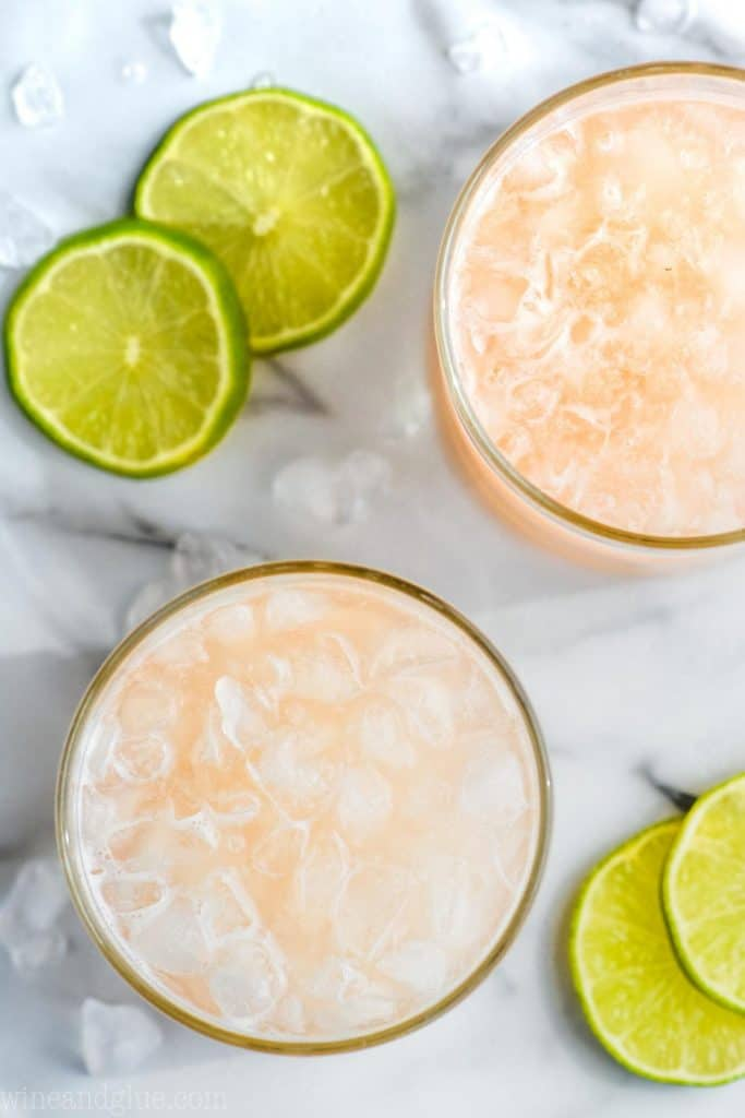 overhead view of two tumblers filled with ice and pink orange paloma drink recipe