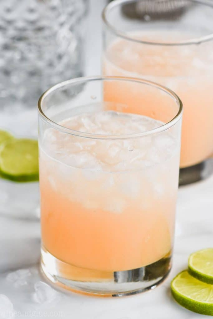 small tumbler filled halfway with ice and a pink orange colored paloma cocktail