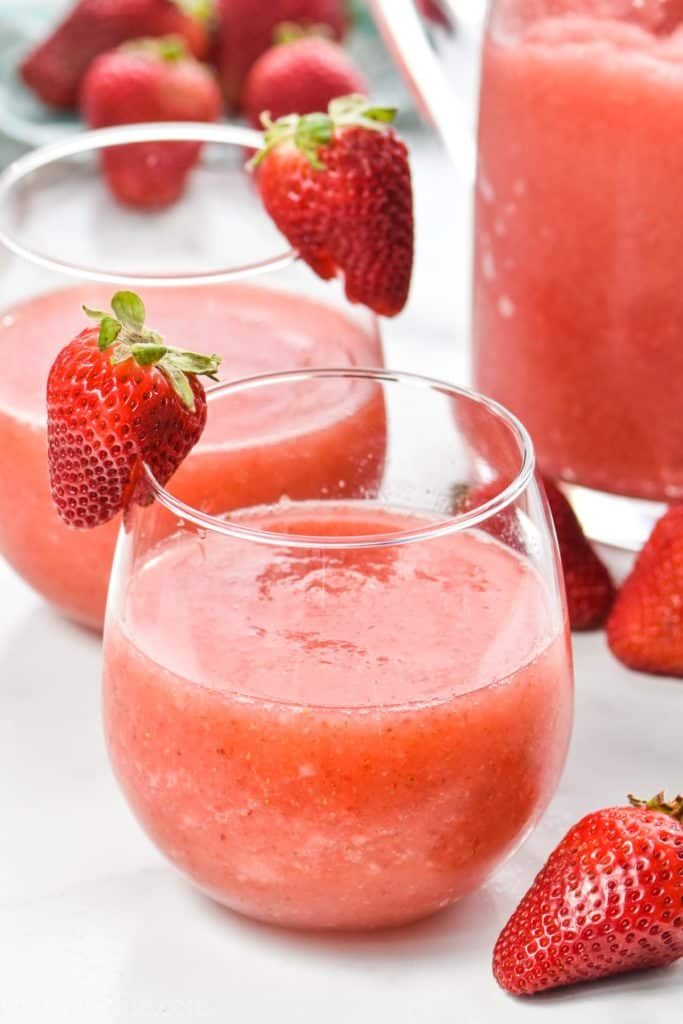 glass of strawberry wine slushie made in a blender with a sliced strawberry on the glass