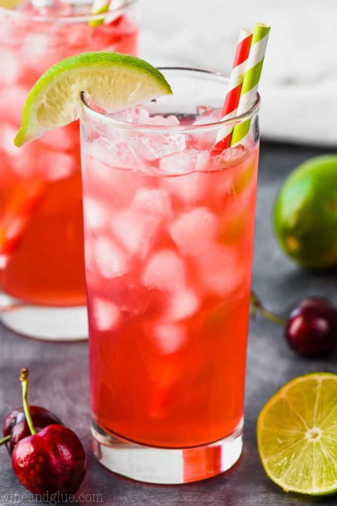 high ball glass full of bright red cherry limeade vodka tonic recipe, garnished with a red striped straw, a green striped straw and a lime wedge