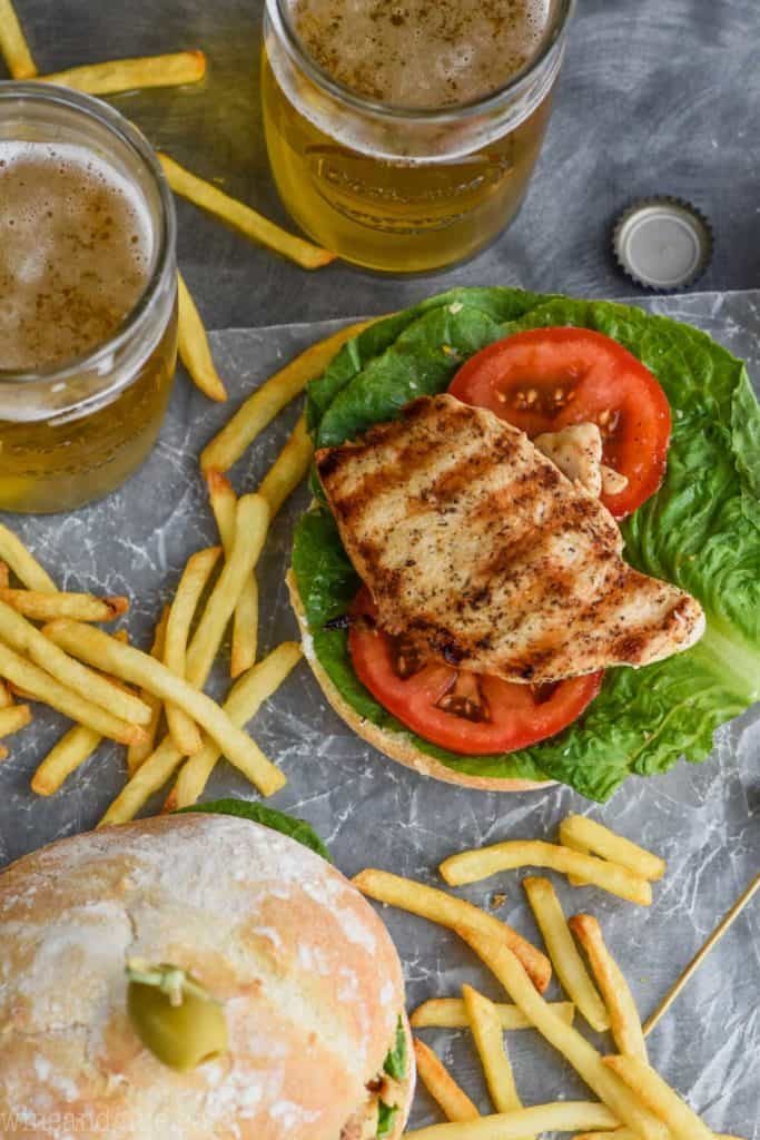 overhead of healthy grilled chicken sandwich recipe on a bun with fries and beers