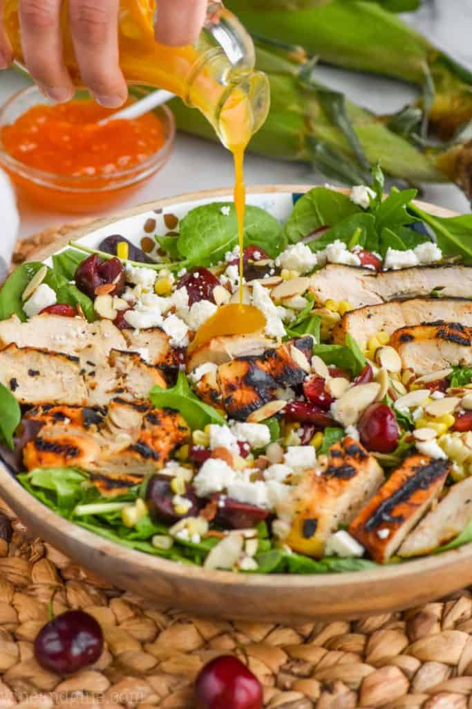 pouring salad dressing on a cherry and corn salad with grilled chicken