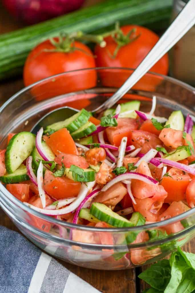 mixing together cucumber, tomato, onion salad in a glass bowl