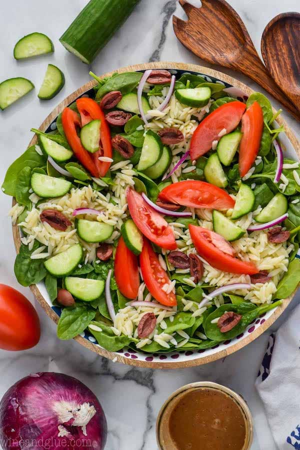 overhead view of greek orzo pasta salad with tomatoes, cucumbers, red onion, orzo and spinach
