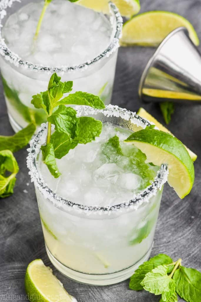 two tumbler glasses filled with a combination of mojito and margarita, rimmed with salt and garnished with a lime and mint