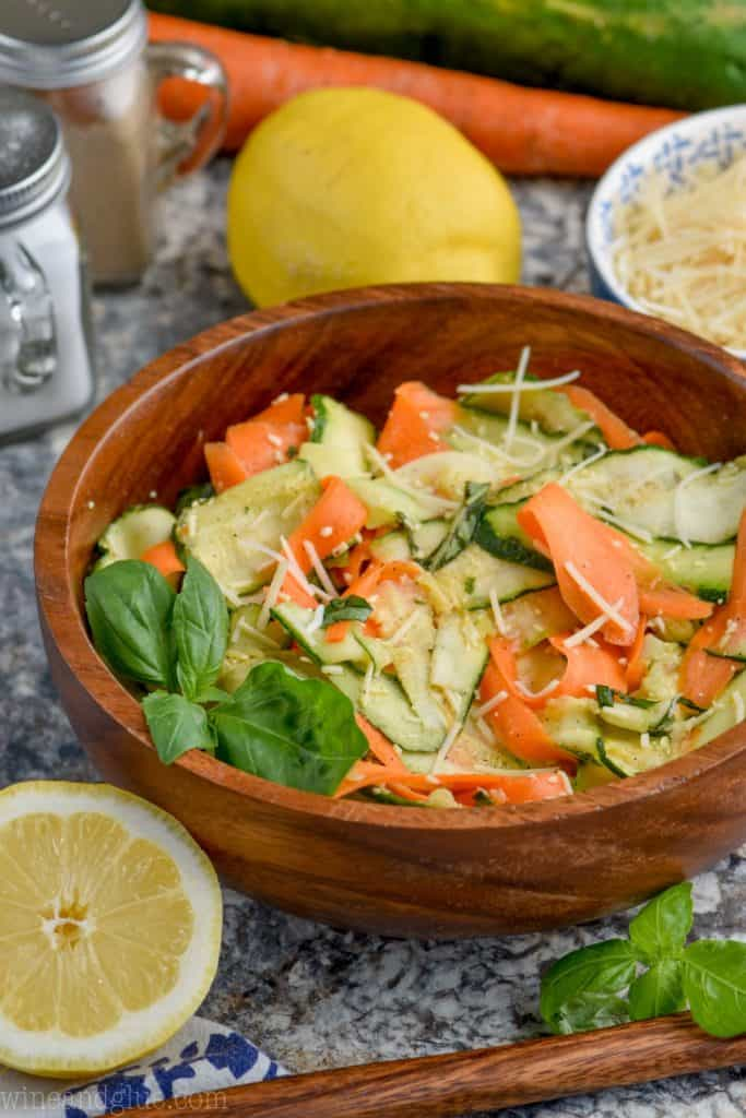 bowl of raw zucchini salad with carrots and parmesan cheese