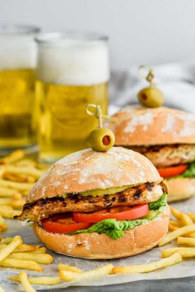 front view of grilled chicken sandwich with beers in the background