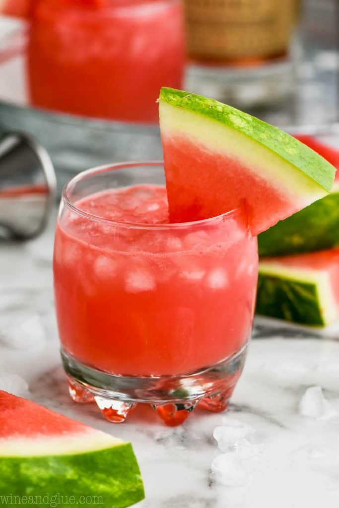 small tumbler full of ice and watermelon vodka tonic, garnished with a watermelon slice