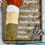 Pinterest graphic of overhead of a baking tray with piles of spices labeled that make up cajun seasoning