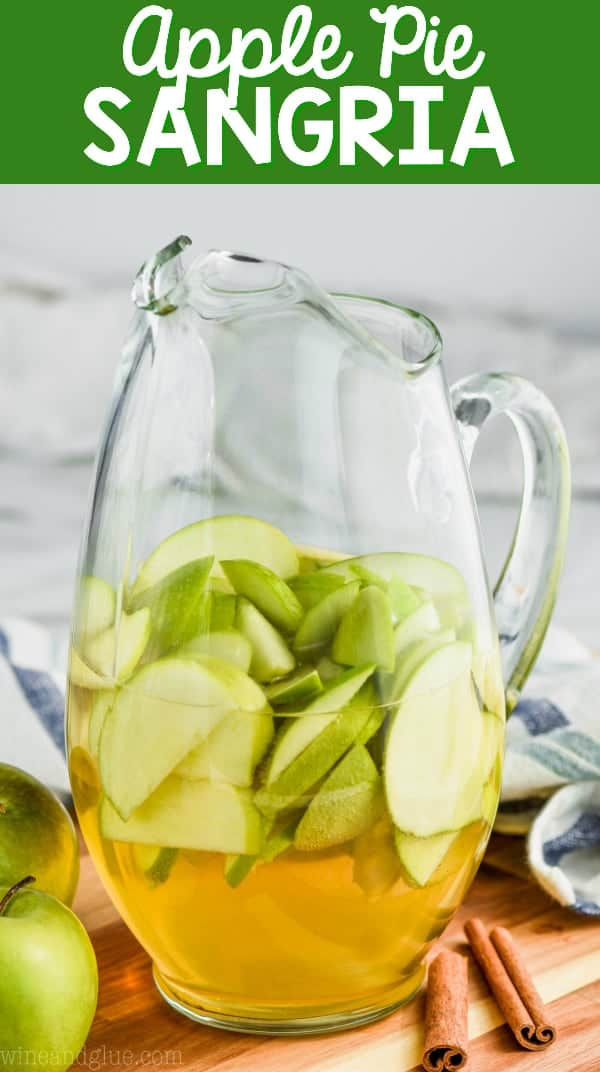 A pitcher with sliced green apples and Apple Pie Sangria