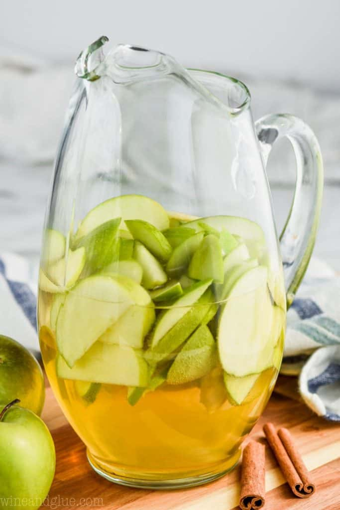 pitcher of apple pie sangria with cut up green apples