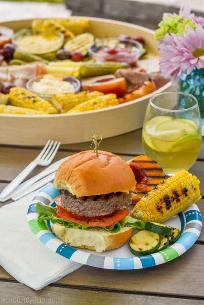 burger and grilled sides on a paper plate