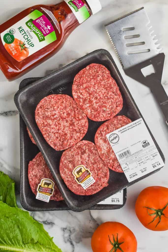 picture of hamburger meat in their packaging surrounded by lettuce, tomatoes, ketchup, and a spatula