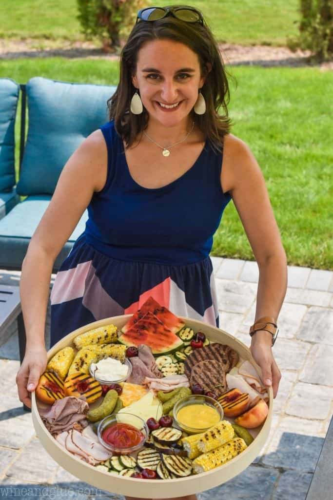 woman holding a giant grilled charcuterie tray