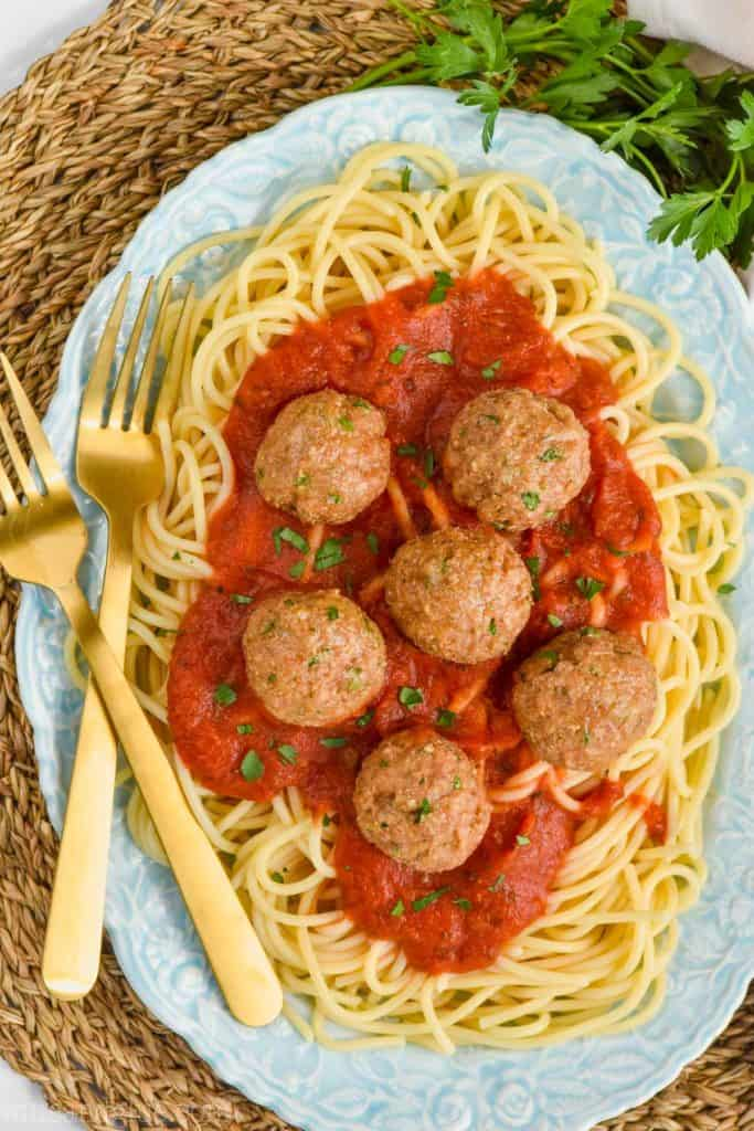 overhead view of baked turkey meatballs on a plate full of sauce and spaghetti