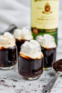 four shots of irish coffee topped with whipped cream