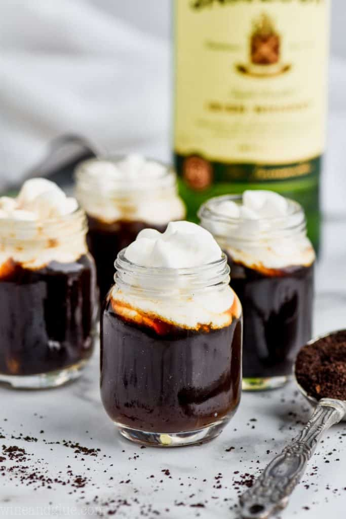 four irish coffee shots topped with whipped cream with a bottle of jameson whiskey in the background