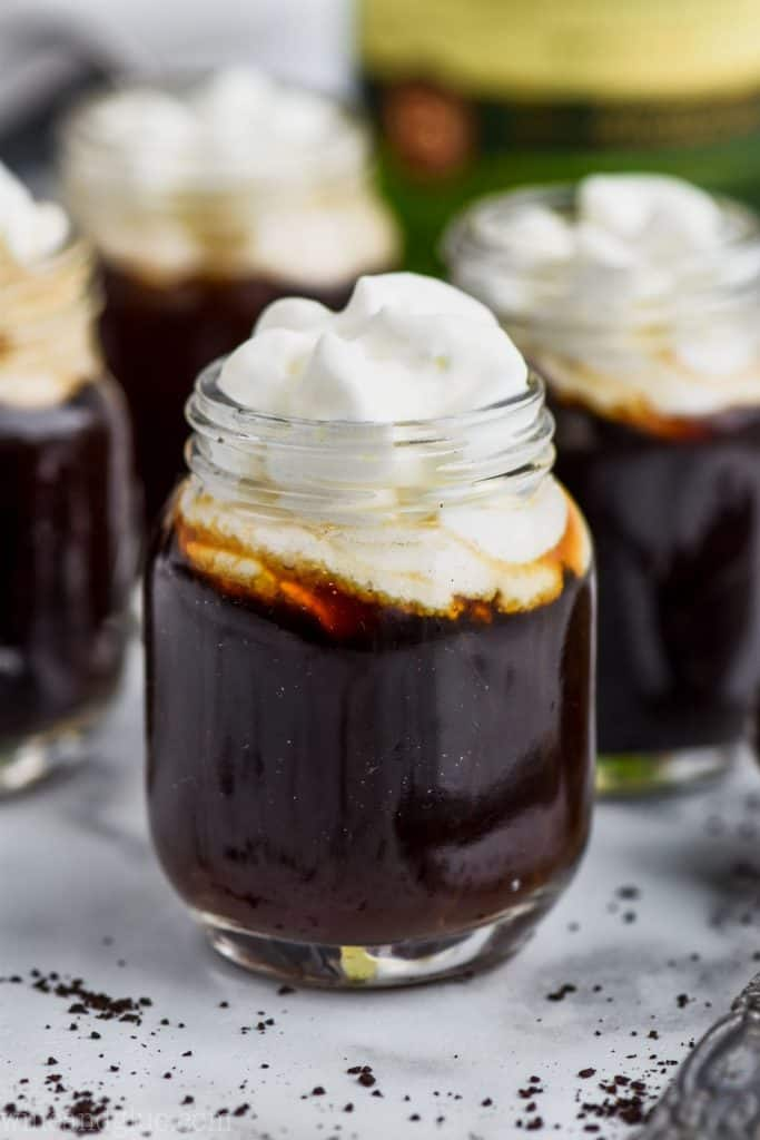 up close video of an irish coffee shot topped with whipped cream with more irish coffee shots in the background