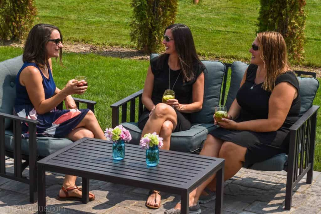 three women sharing wine at labor day party