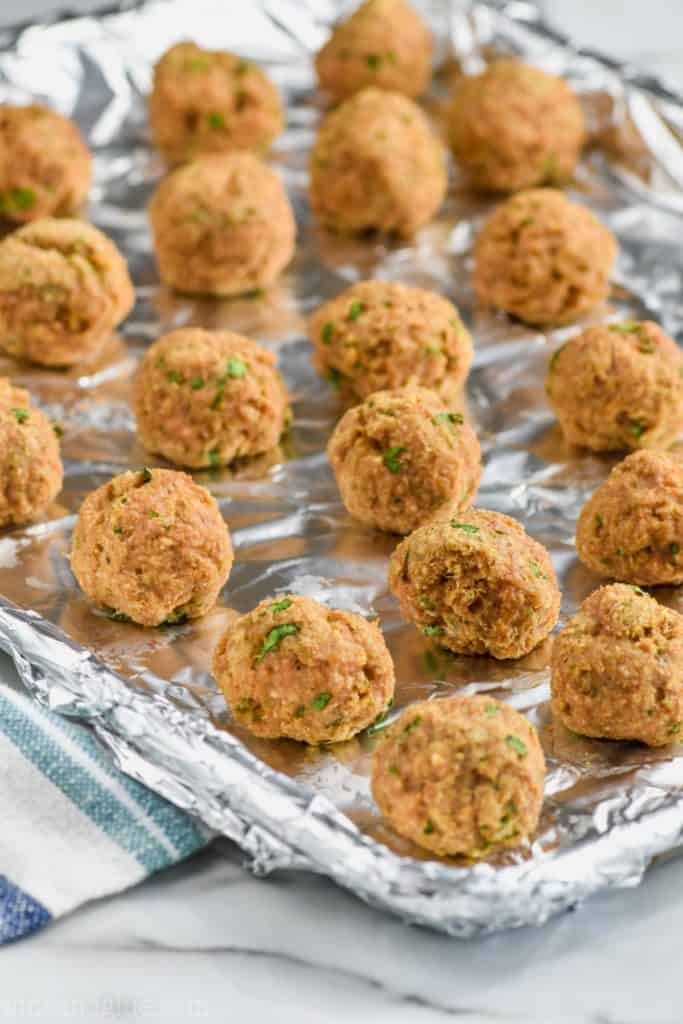 baked turkey meatballs lined up on a baking sheet
