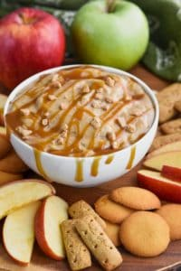 bowl of caramel apple dip recipe dripping from the sides with caramel sauce