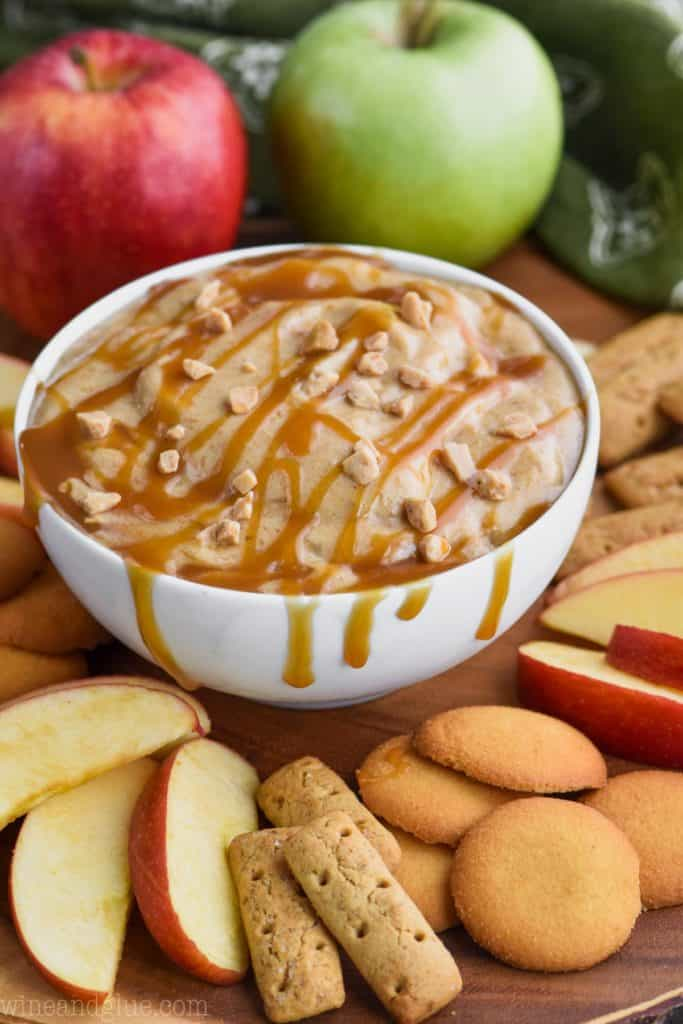 In a small white bowl, the Caramel Apple Dip sauce is topped with caramel and toffee bits and surrounded with apples, graham crackers, and wafers.