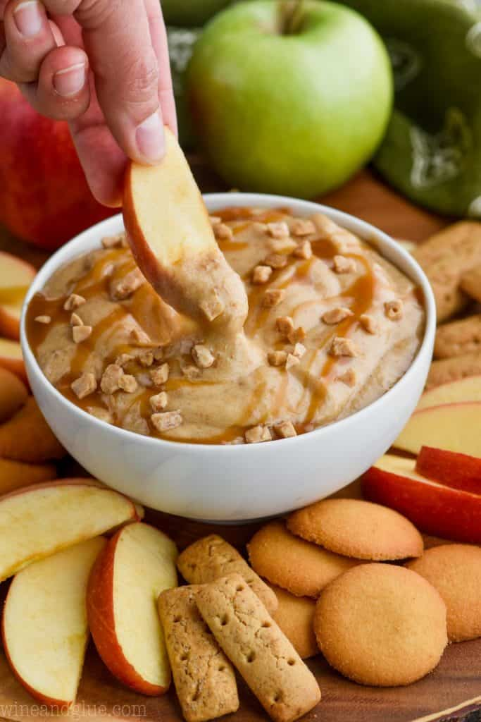 an apple being dipped into cream cheese caramel apple dip