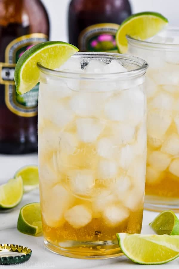 tall glass filled with ice and dark and stormy recipe, garnished with a lime wedge