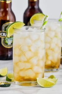 two tall glasses filled with dark and stormy cocktails and garnished with lime wedges with striped straws and ginger beer bottles in the background